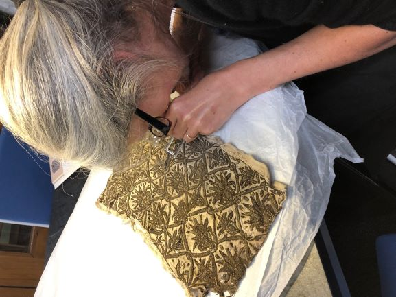 Textile researcher and Author of 'Elizabethan Stitches', Jacqui Carey examining a piece of Elizabethan fabric at the Weald & Downland Living Museum.