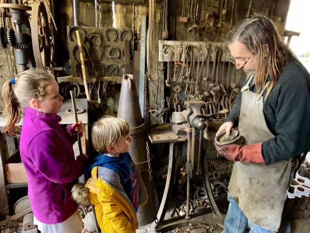 Blacksmith volunteer teaching children visitors